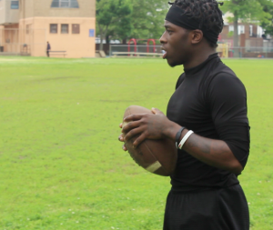 Quarterback, Neante Harif, motivates and watches on as team completes footwork drill.