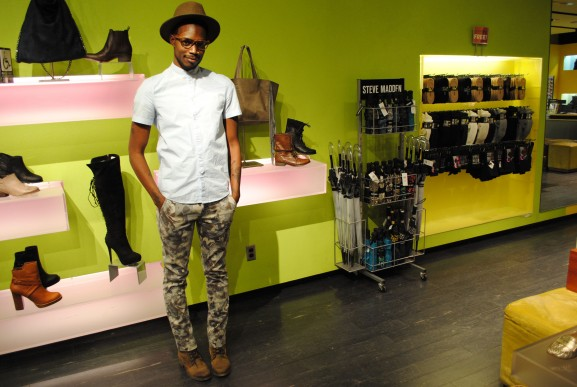 Que in army green pants poses against a wall of shoes.