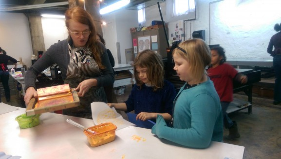 Education coordinator Lauren Pakradooni assists two girls with their screen printing.