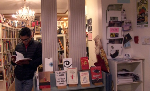 A patron at The Spiral Bookcase browses one of the recommended readings.