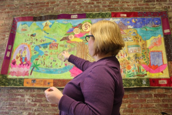 Juliane Ramic, senior director for refugee and community integration at NSC, points to a mural created by Bhutanese refugees and given as a gift to the nonprofit.