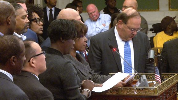 Brown speaks among other representatives at a City Council session.