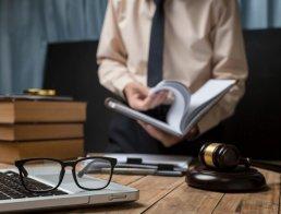 homem folheando livro e mesa com vários objetos