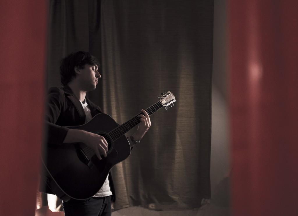 Simon Jutras alias MCLEAN jouant de la guitare devant des rideaux fermés