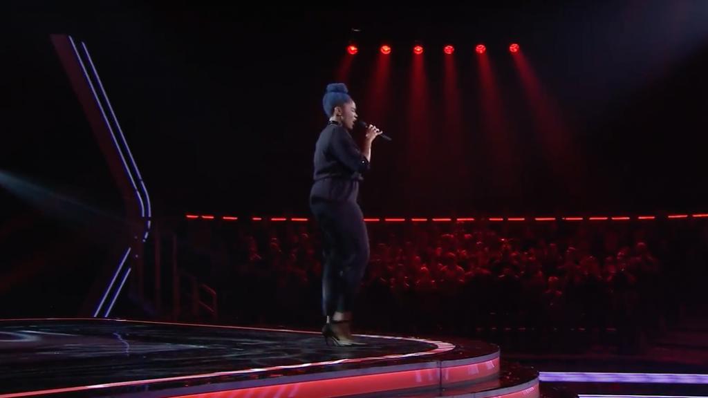 Karimah est vêtue de noire et à la chevelure bleue. Elle chante sur la scène de La Voix.