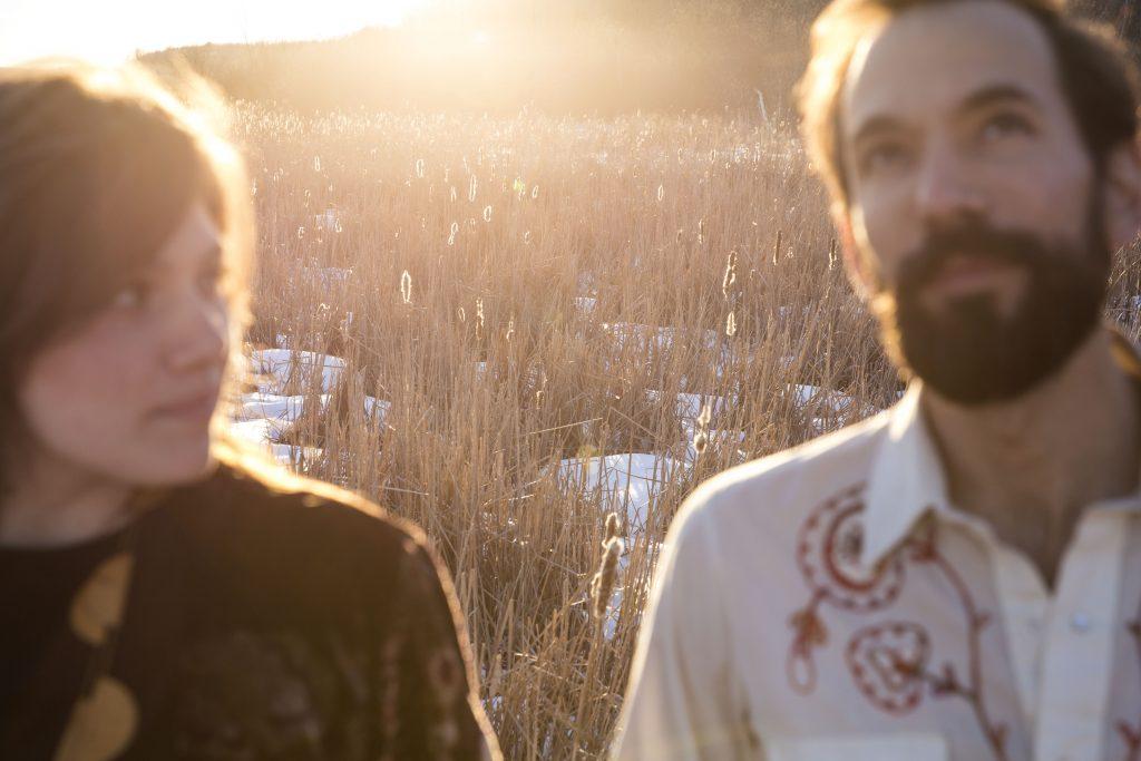 Kaitlin et Alex en avant plan, devant un coucher de soleil, dans un champ de longues herbes séché avec de la neige au sol. Kaitlin regarde Alex, qui regarde vers le ciel.
