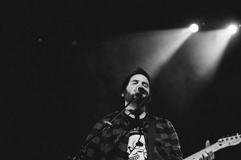 En noir et blanc, Marc-Antoine Joly devant un micro, guitare à la main, il chante les yeux fermés, sur une scène, éclairé par un projecteur.