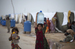Caption: In Karachi, the capital of Pakistan's Sindh province, girls carry large bottles of water in a camp for people displaced by flooding., Credit: © UNICEF/NYHQ2010-1635/Ramoneda