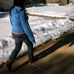 Caption: Brenda, 19, walks through her Minneapolis neighborhood. She's been living as an illegal immigrant in Minnesota since she was 7 years old., Credit: MPR Photo/Jeff Thompson