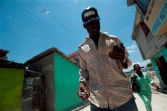 Caption: Radio journalist Makenson Rmy walks through Saint Martin, the slum where he grew up. He follows tips that sources send him by text message, Credit: Charles Eckert