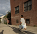 Caption: Young man walking in Brooklyn, Credit: Michael Premo