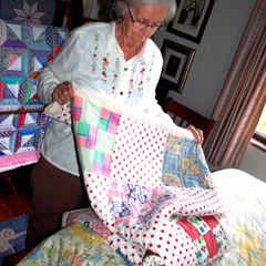 Caption: Ruth Ellis displaying her award-winning Feed Sack Quilt, Credit: Reuben Ellis