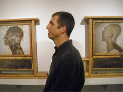 "Caption: Artist Brigham Dimick with part of ""Waxworks 2,"" a series of three self-portraits that include observation hives with live honeybees., Credit: (UMSL/Terry Suhre)"