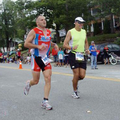 Caption: John Rymes (l) running in the Lake Placid Ironman Triathlon, 2011