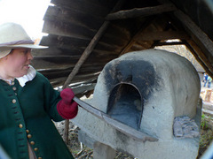 Caption: A cast member at Plimoth Plantation bakes bread in the village oven