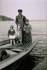 Caption: Early North Shore commercial fisherman with children and lake trout., Credit: Photo courtesy of the North Shore Commercial Fishing Museum