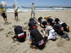 Caption: Environmental activists with flags on their backs bury their heads in the sand on Durban's beachfront, highlighting nations that are failing to effectively prevent climate change. , Credit: Mike Hutchings/Reuters) From TakePart.com: Ocean Gets No Respect From Durban