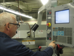 Caption: Instructor Steve Henkelman programs a CNC machine at Grand Rapids Community College., Credit: Dustin Dwyer