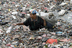 Caption: An Indonesian collecting plastic goods amidst a pile of rubbish.  Ciliwung River, Jakarta, Indonesia., Credit: Ardiles Rante
