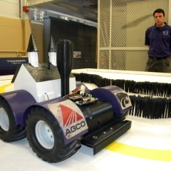 Caption: Brent Ware, a member of the robotics team at Kansas State, stands next to a planting robot that won a national competition. , Credit: Jeremy Bernfeld/Harvest Public Media