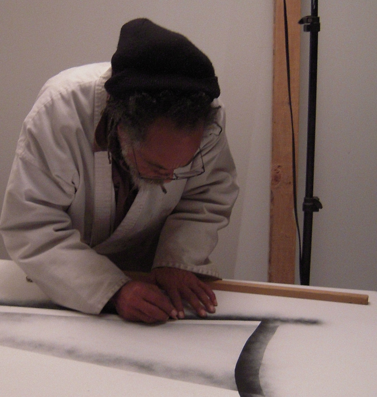 Caption: Artist Samaj works on a painting for his Entry/Dropline series.