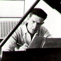 Caption: John Cage composing at piano
