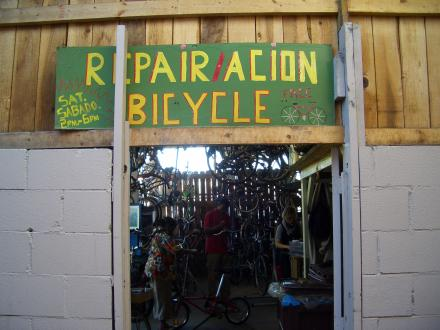 Caption: Entrance to the shop, with volunteer-painted sign. Inside: Kathleen Mills, Steven Hobdy and Morgan Kanninen, Credit: Jen Chien