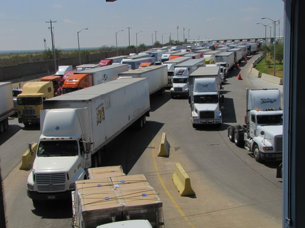 Caption: Trucks line up for for inspection at the World Trade Bridge in Laredo, Texas. About 5,000 trucks per day travel through this commercial crossing., Credit: Monica Ortiz Uribe
