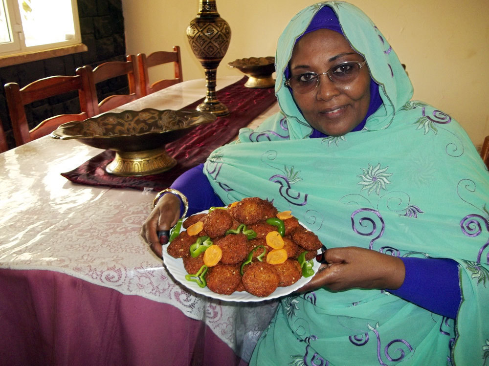 Caption: The reporter's mother, Nawal Elbager, of Khartoum, Sudan, shows off her falafel.