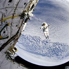 Caption: Backdropped against the blue and white Earth 130 nautical miles below, astronaut Mark C. Lee tests the new Simplified Aid for EVA Rescue (SAFER) system. , Credit: NASA
