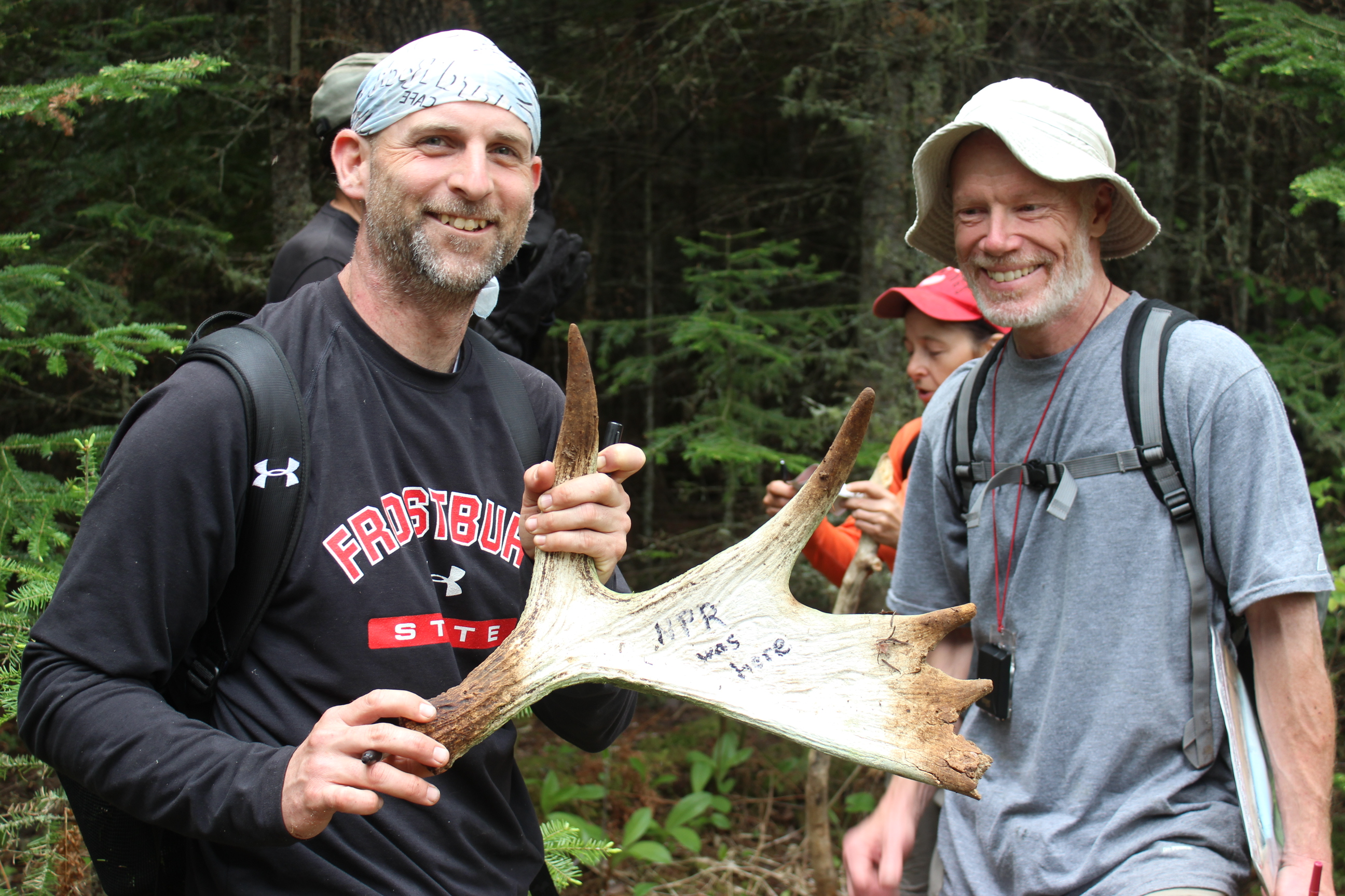 Caption: Moosewatch volunteer Dave Beck holds up a marked antler. Team leader Jeff Holden looks on. They mark the antlers and hang them in a tree so others know the antler has been found and documented., Credit: Mark Brush