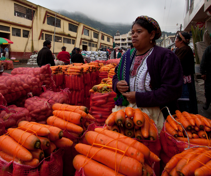 Caption: A woman in Almolonga, Guatemala, selling carrots and potatos wholesale., Credit: Jesse Dukes