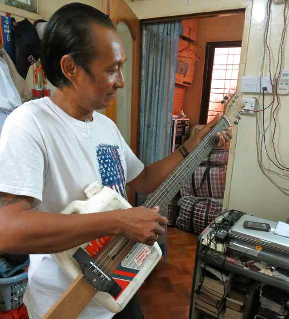Caption: Former Political Prisoner Win Maw plays a guitar he made in prison