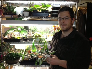 Caption: Kenneth Moore next to his tower of plants, in his basement apartment in Washington DC