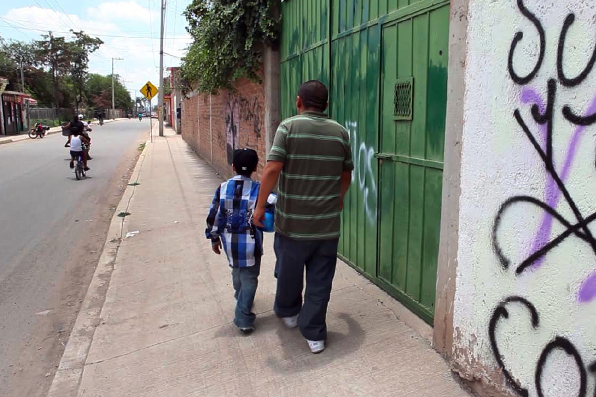 Caption: An American boy walks down a street in Guanajuato, Mexico with his father, a deported Mexican national., Credit: Erin Siegal McIntyre