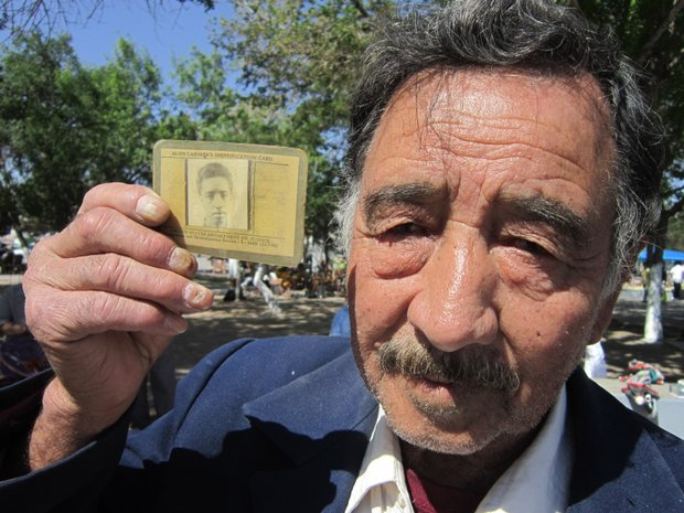 Caption: A former Bracero holds up his identification card from his days as a guest worker in the United States. , Credit: Monica Ortiz Uribe