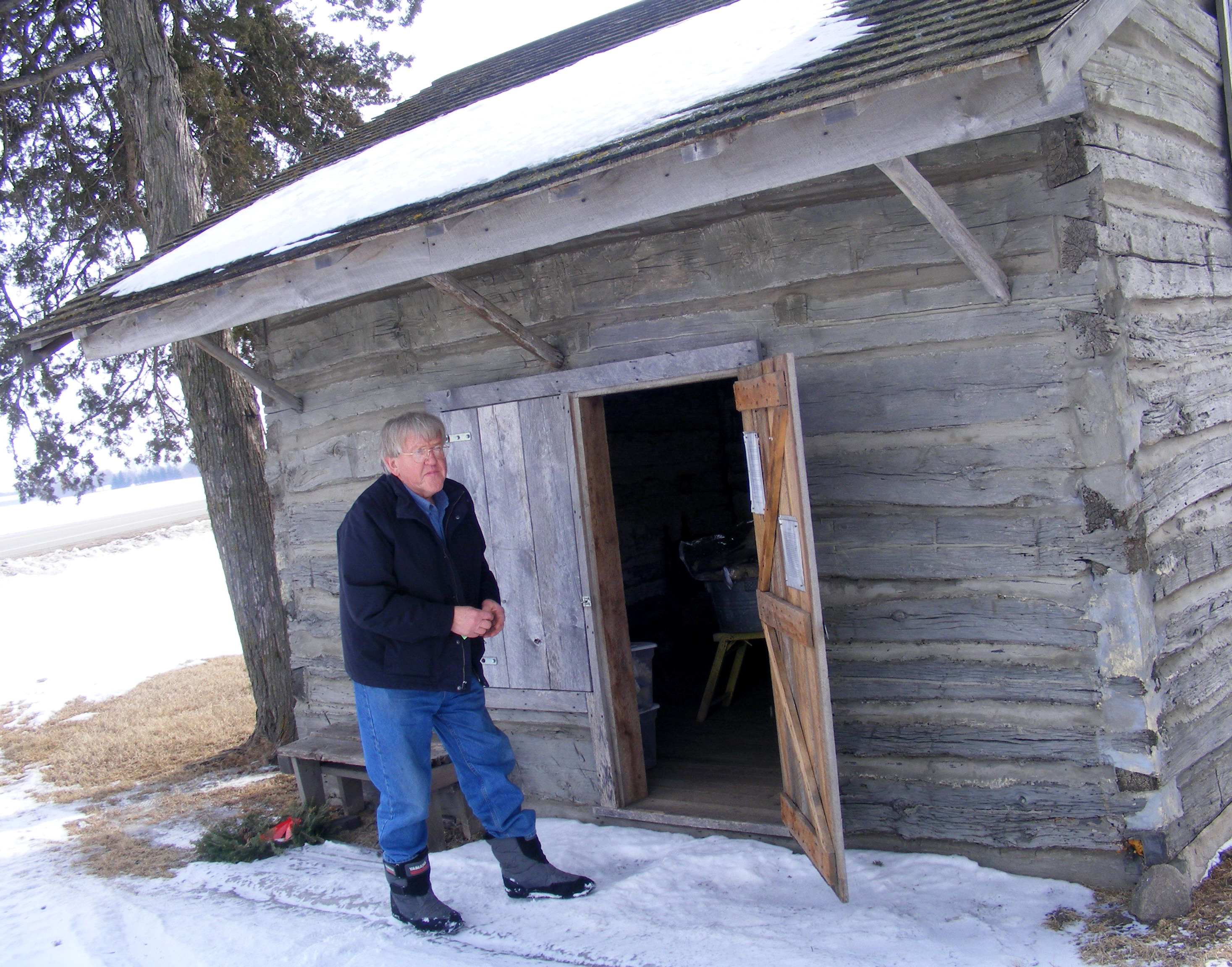 Caption: Harvey Barberg of Cokato Stands By the One-room Cabin Where Ancestors Spent Their First Winter