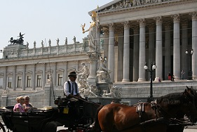 Caption: A carriage passes by the front of the Austrian Parliament traveling along the Ringstrasse., Credit: Photo by: Wendy Hendrickson