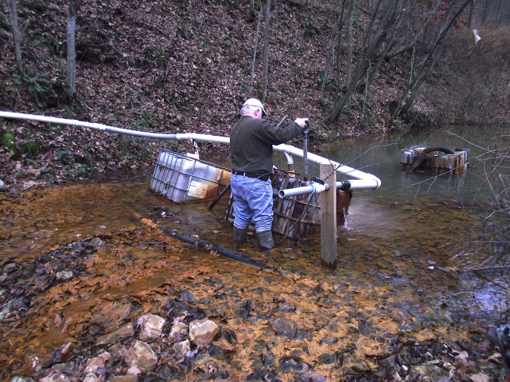 Caption: Mike King of the Morris Creek Watershed Association working on a homemade treatment system for Acid Mine Drainage, responsible for the orange muck polluting Morris Creek