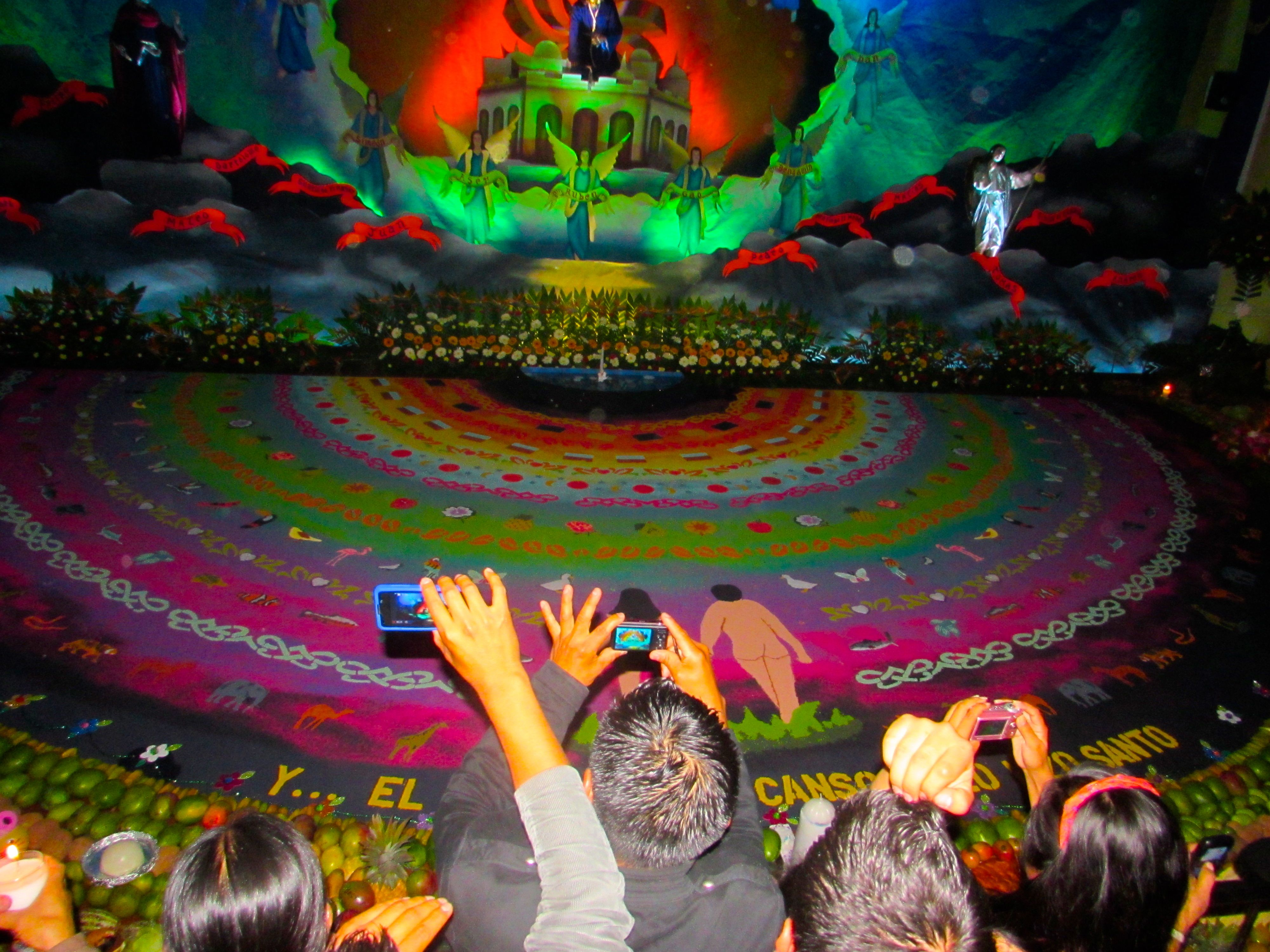 Caption: Onlookers press against the barrier to take photos of the display depicting the biblical creation of the world in the church of San Bartolome Bacerra, Friday., Credit: Benjamin Reeves