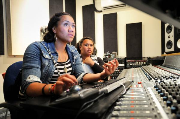 Caption: Students from Girls on the Mic at Womens Audio Mission work on a project using the 40-channel mixing console once used by Soundgarden., Credit: Womens Audio Mission