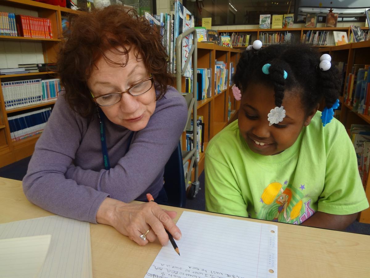 Caption: Volunteer Pat Gold (left) and Tiara Brooks work on a story at an 826 Michigan writing workshop at Adams STEM Academy in Ypsilanti., Credit: JENNIFER GUERRA / MICHIGAN RADIO
