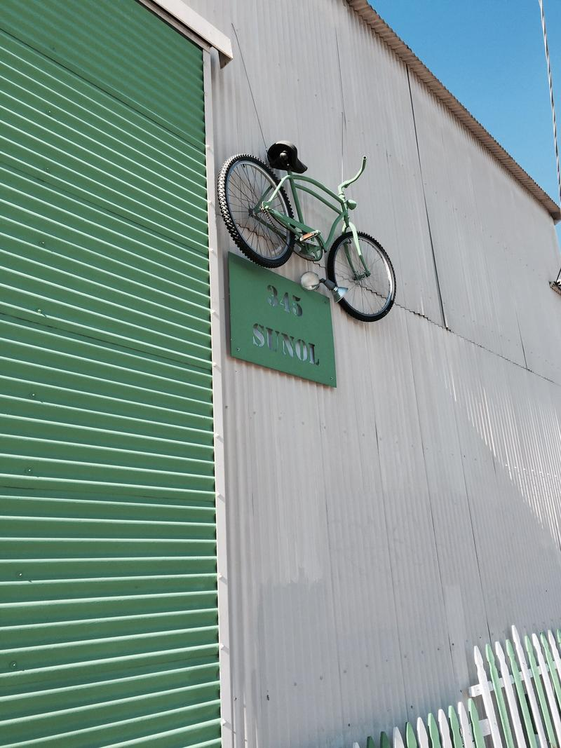 Caption: A bike hangs on the wall outside Good Karma Bikes in San Jose, Credit: Leslie Griffy