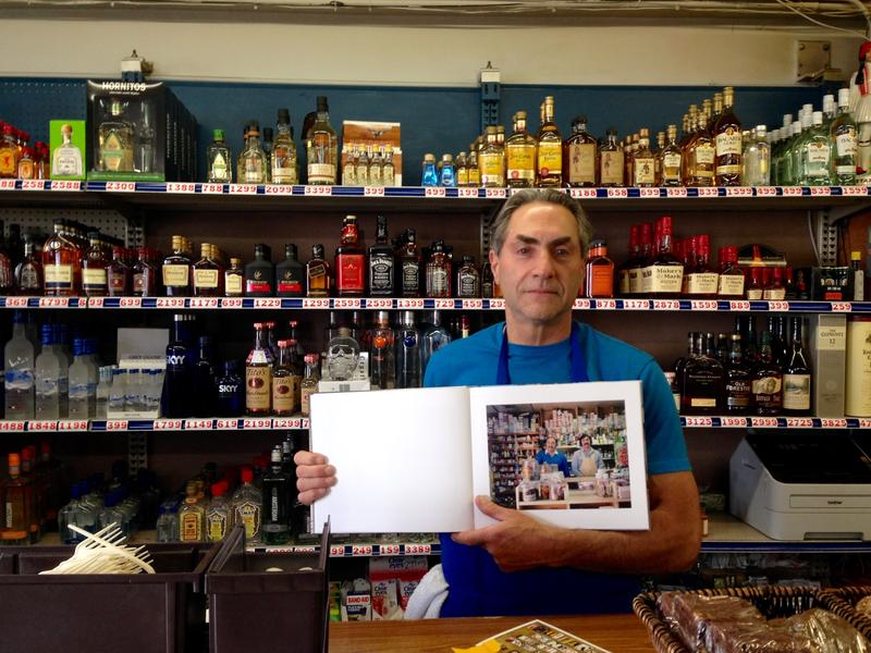 Caption: Dave Zouzounis stands behind the counter at Ted's Market, holding a book with Janet Delaney's photograph of him and his dad, Credit: Angela Johnston