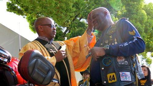 Caption: Reverend Jeff Moore blesses biker, Credit: Leila Day