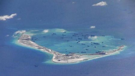 Caption: Chinese dredging vessels in the waters around Mischief Reef in the disputed Spratly Islands. Still shot is from video taken by a U.S. Navy P-8A Poseidon surveillance aircraft (May 2015). , Credit: REUTERS/U.S. Navy/Handout via Reuters.