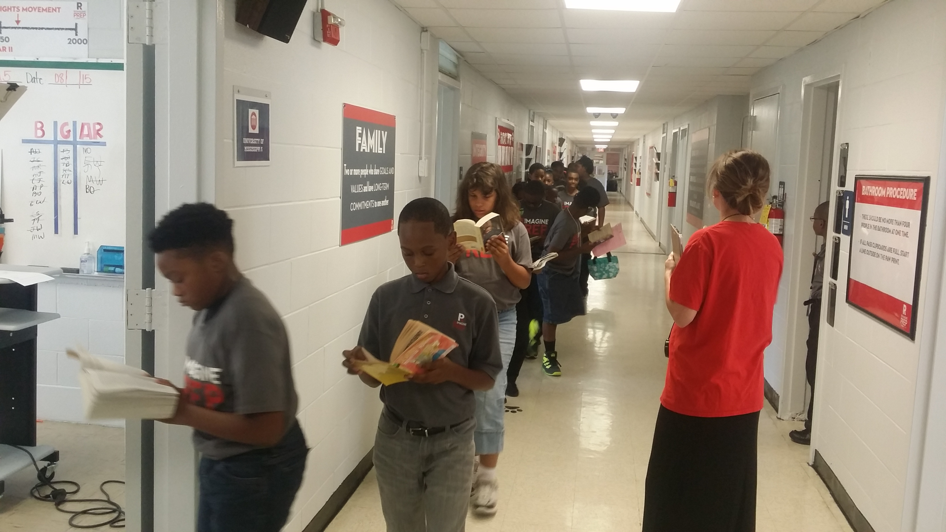 Caption: Students at ReImagine Prep in Jackson, Mississippi, read books on their way to class, Credit: Paul Boger
