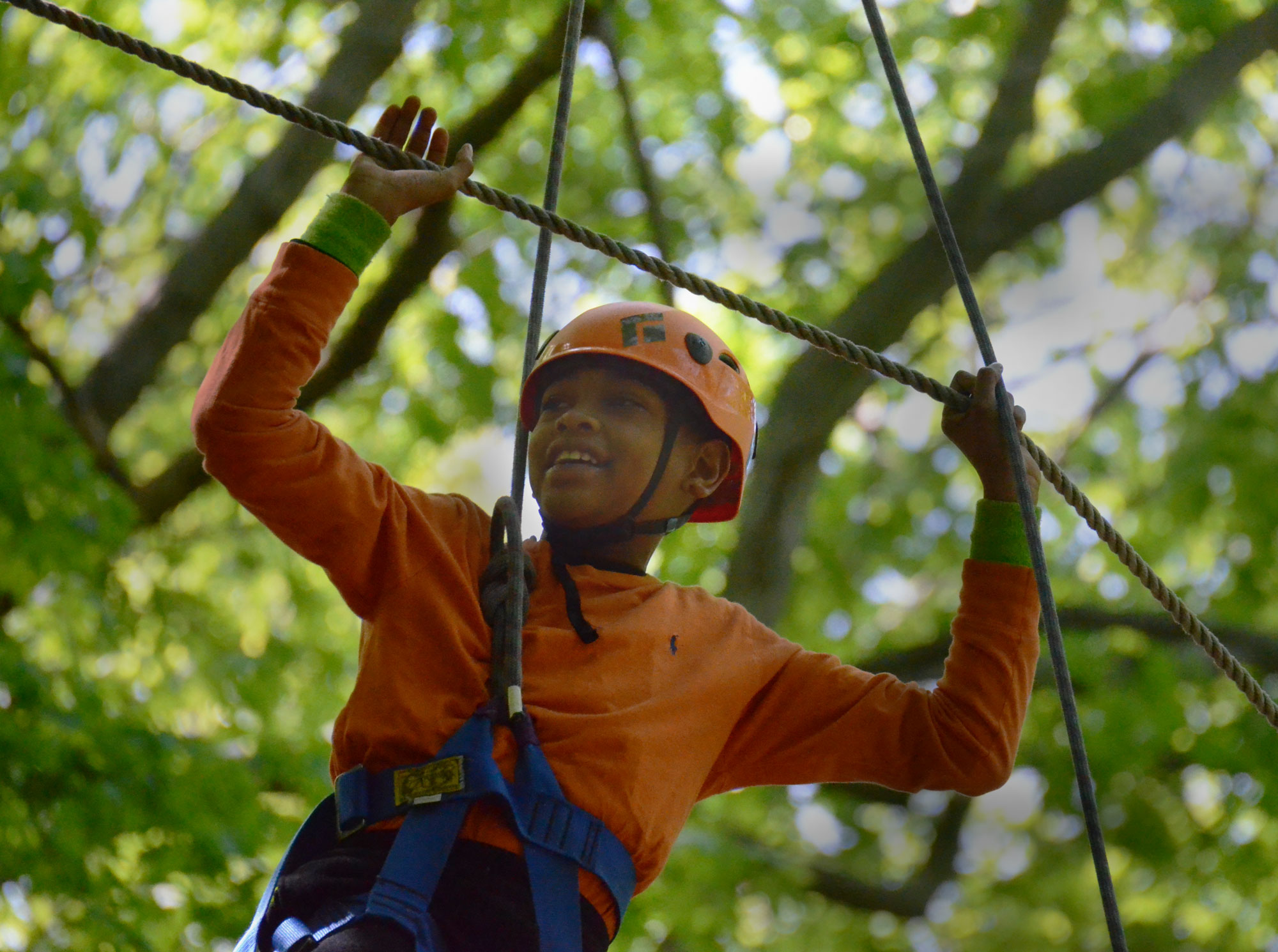 Caption: A student at the Metropolitan Expeditionary Learning School in New York conquers a high ropes course., Credit: Stephen Smith