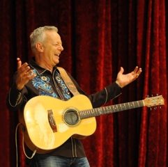 Caption: Guitar master Tommy Emmanuel having fun on the WoodSongs Stage.