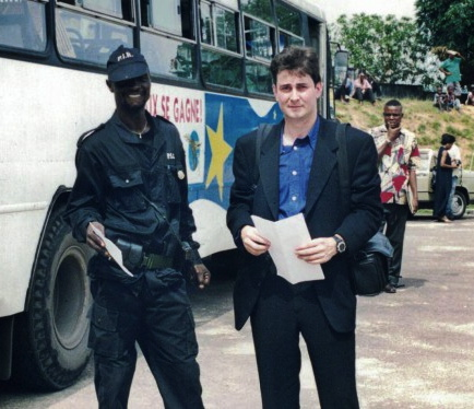 Caption: Sasha Chanoff stands next to a hired armed guard in the safe compound outside Kinshasa.